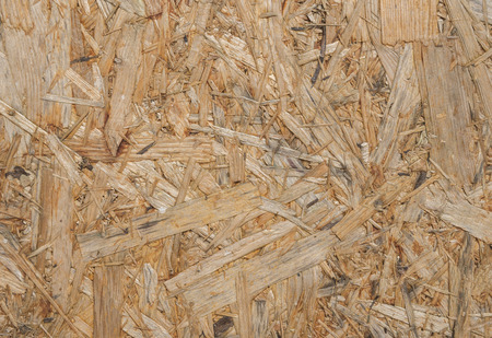 oriented: Oriented Strand Board. Wooden panel made of pressed of sandy brown wood shavings as background vertical view closeup Stock Photo