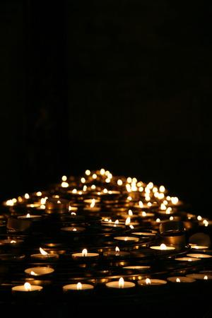candela: Candele di preghiera illuminano al buio in una chiesa, coppie, in Francia.