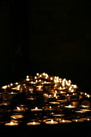 christian candle: Prayer candles light up the dark in a church,Pairs , France. Stock Photo