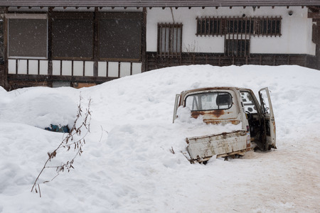 leavings: Snow falling with old rusty small truck car under the snow covered