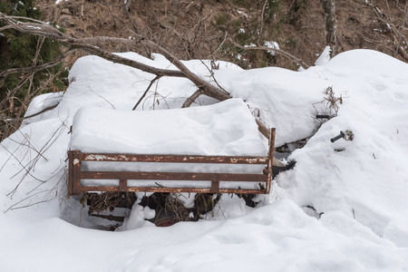 leavings: Old rusty wheelbarrow under the snow covered