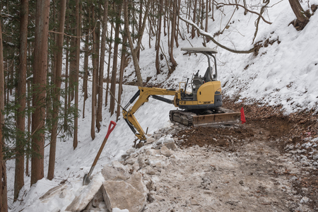 tree removal service: The rusty old tractor wait to clears snow from the way in winter mountain.