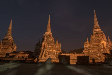 Ancient ruins of the temple Wat Phra Sri Sanphet  national historic site with lights show at night time in Ayutthaya, Thailand.