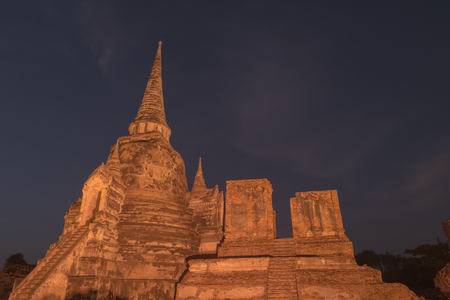 Ancient ruins of the temple Wat Phra Sri Sanphet national historic site with lights show at twilight time in Ayutthaya, Thailand.
