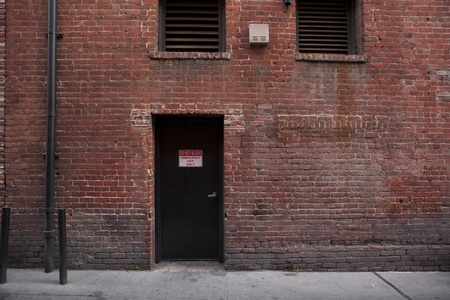 Back door entrance to an old brick building from the alley Stock fotó - 18427768