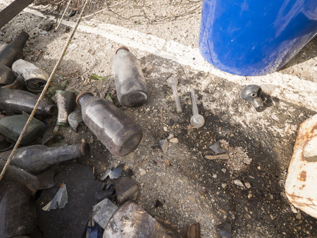 A close up of bottles and crack pipes left on the ground. Stock Photo