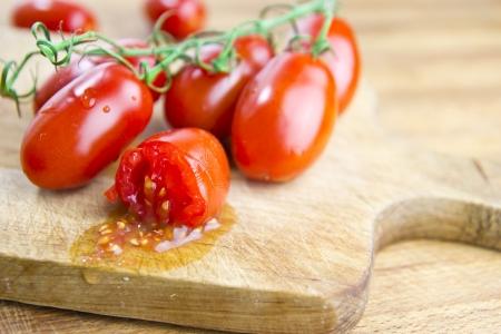fresh plum tomatoes over cutting board closeup