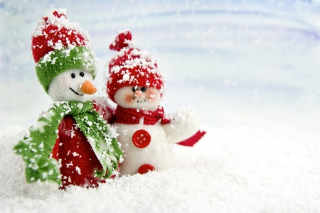 two smiling snowmen friends in the snow - no name toy Stock Photo