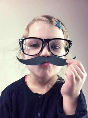 Child with paper mustaches and big glasses