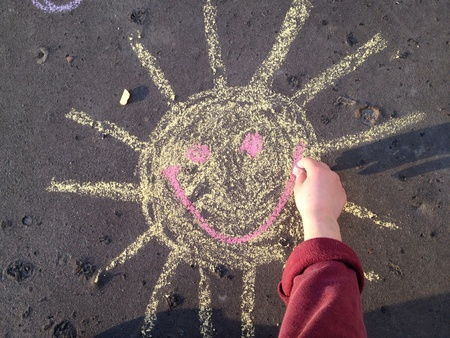 Hand drawing smiling sun with a chalk