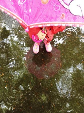 botas de lluvia: Niño en la lluvia Foto de archivo