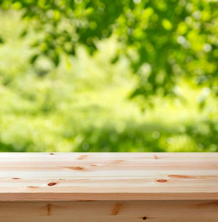 ぼかした庭に対して背景の木のテーブル