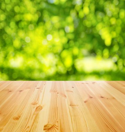 prázdný dřevěný stůl proti slunné zahradě na pozadí Reklamní fotografie