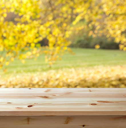 Empty wooden table against autumn background