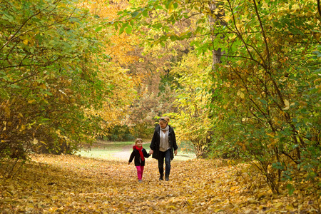 autumn in the park: mother walking with daughter in autumn park