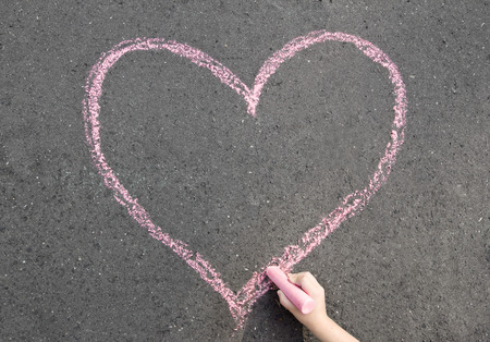child hand drawing heart on the street