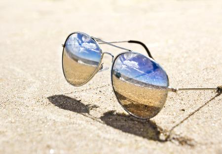 zee landschap weerspiegelt in de zonnebril op het strand