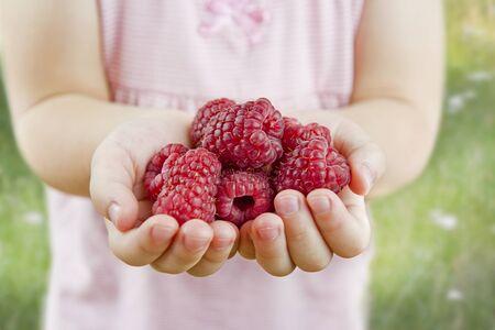 raspberry dress: little girl holding raspberries