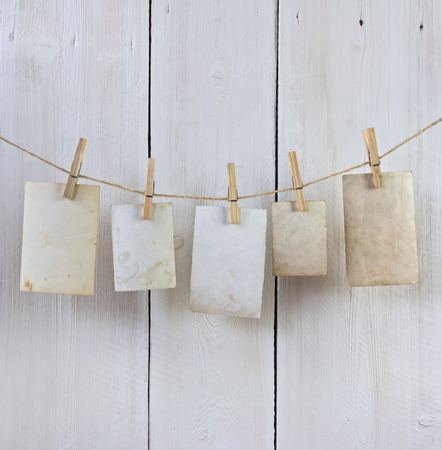 old photos hanging on the rope with a clothespin against white planks
