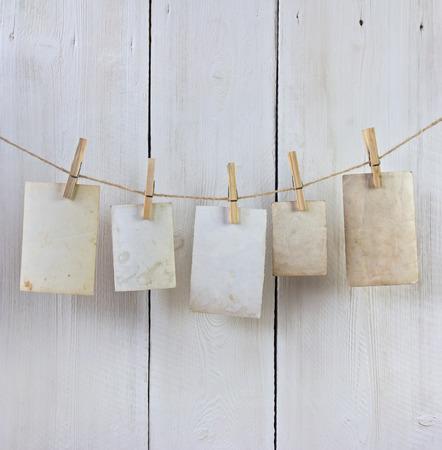 흰색 판자에 대 한 clothespin와 로프에 매달려 오래 된 사진