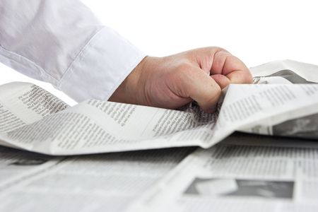turmoil: Bad news. Hand crumpling a newspaper. Stock Photo
