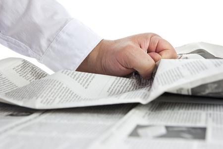 office politics: Bad news. Hand crumpling a newspaper. Stock Photo