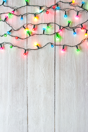 Christmas lights over white painted planks for background