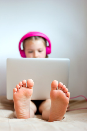 Feet of little girl using laptop Stock Photo