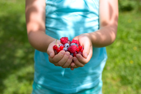 Girl holding fresh fruits in her hands Stock Photo