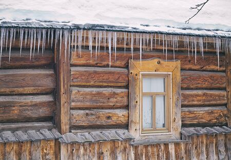 Icicles hanging from the roof of the old, rustic house. Banco de Imagens