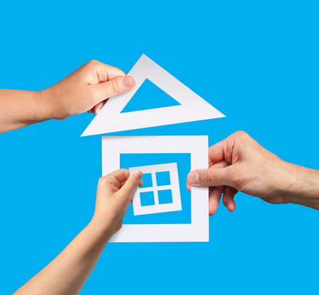 Hands of family holding a model of paper house. Idea of planning to have a home. Standard-Bild