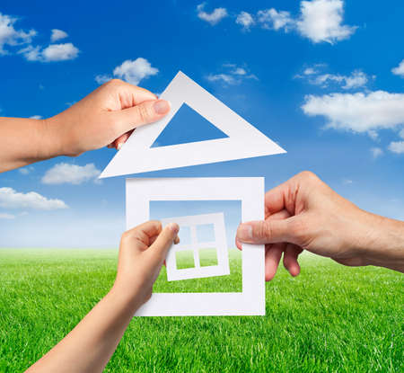 Hands of family holding a model of paper house against the sunny landscape. Idea of planning to have a home. Standard-Bild