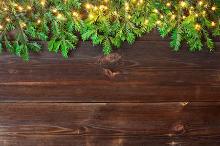 Fir branches and Christmas lights on wooden rustic planks. Christmas background. High angle view. 免版税图像