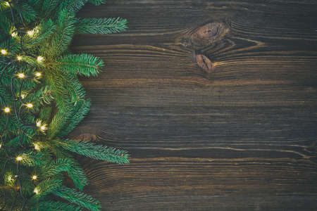 Christmas decoration. Fir tree and christmas lights on rustic, wooden background. High angle view. 免版税图像