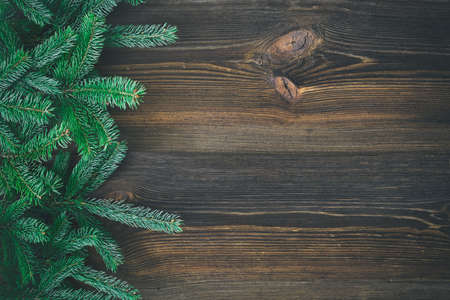 Christmas decoration. Fir tree branches on rustic, wooden background. High angle view.