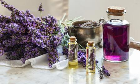 Butelki z olejkiem lawendowym, naturalna koncepcja kosmetyki ziołowej z kwiatami lawendy flatlay na kamiennym tle