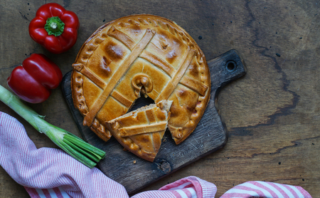 Empanada de atun, Traditional pie stuffed with tuna fish typical from Galicia, Spain, top view, wooden background