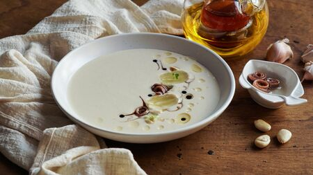 ajo blanco, spanish typical cold soup, made of almonds and garlic with olive oil and bread. white garlic soup Фото со стока - 132113400