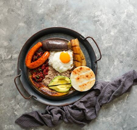 Colombian food. Bandeja paisa, typical dish at the Antioquia region of Colombia - chicharrón (fried pork belly), black pudding, sausage, arepa, beans, fried plantain, avocado egg, and rice.