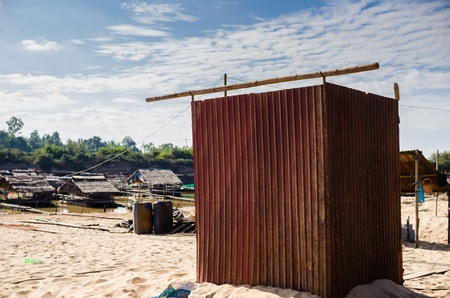 Outdoor toilet on the sand beside the river