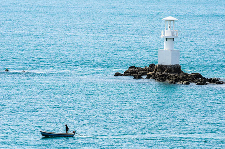 White Lighthouse on the sea and blue sky in Thailand photo