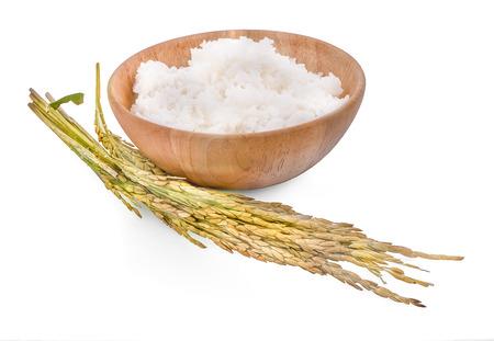 Arroz blanco (arroz jazmín tailandés) en un tazón de madera y arroz sin moler aislado sobre fondo blanco. Foto de archivo