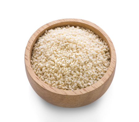 wooden bowl of sesame seeds and a scoop on a white background
