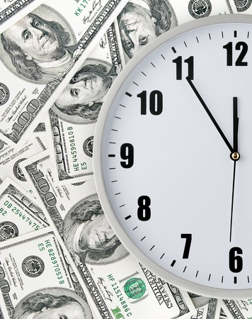 clock with hand on money background Stock Photo - 14388148