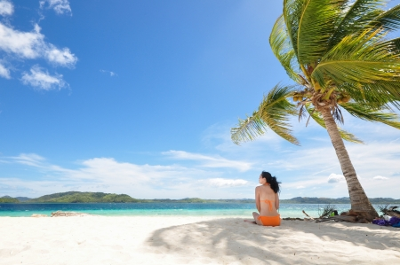 Single young bikini girl sits in the shadow of a coconut tree on white beach photo