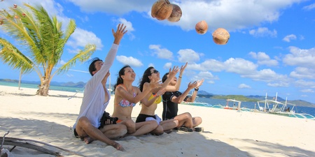 Two happy young couples sit on tropical white beach and play with coconuts as balls, with background of beautiful blue sky and cloud and ocean. Shot on Pass Island, Coron, Palawan, Philippines photo