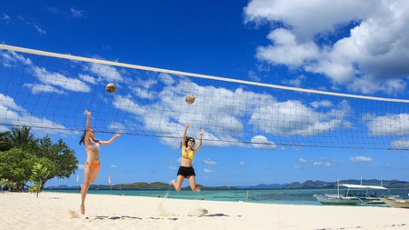 Two young girls jump and play volleyball using coconuts on white beach, with background of beautiful blue sky and crystal water. Shot on Pass Island, Coron, Palawan, Philippines photo