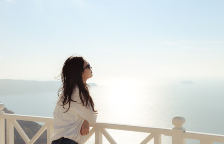 stand: beautiful young girl on cliff balcony with sun glasses looks at sea horizon, in a wine factory at Santorini, Greece