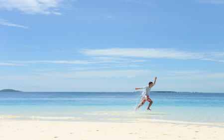 Side portrait of single young man running and jumping on tropical white sand beach photo