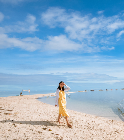 Single young girl looking at the camera when walking on long curving stretch of narrow white sand beach during low tides  Shot on Virgin Island, Panglao, Bohol, Philippines, known to many locals as the ?hidden oasis?